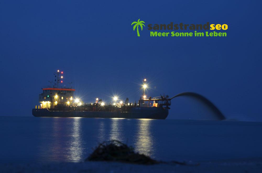 Sand-Pump-Schiff vorm Strand bei Nacht